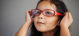 A young girl trying on a pair of bright red glasses.