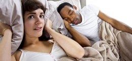 A woman holds a pillow over her ears to ignore her husband's snoring