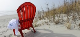 A red chair sits on the beach, holding a Tidelands Health physician jacket and a stethescope.