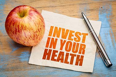 "Napkin reads ""Invest In Your Health"" with apple, pen nearby"