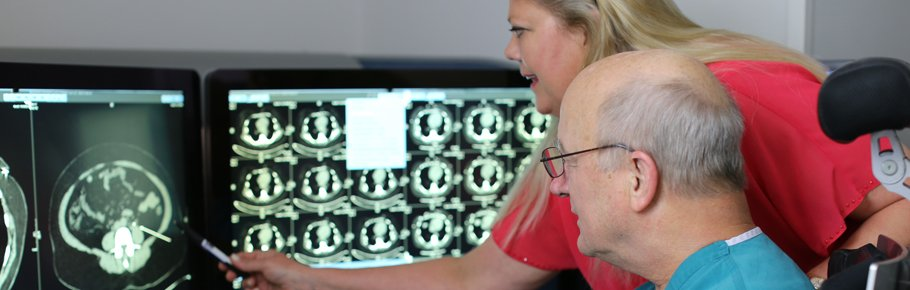 Two radiologists review a montior image.