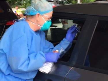 A Tidelands Health medical professional tests for COVID-19 during drive-through clinic June 13 at Pelicans stadium.