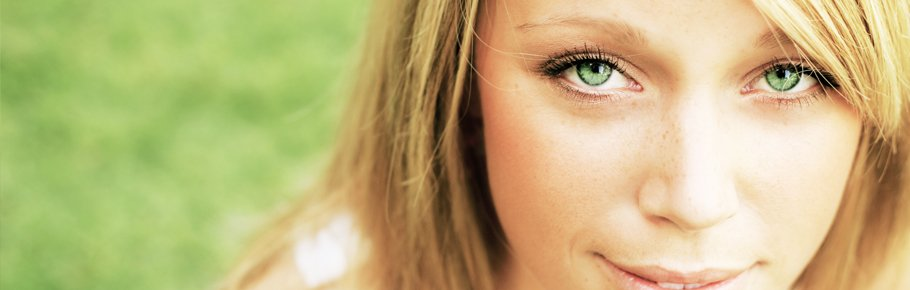 A woman with bright green eyes stares into the camera.