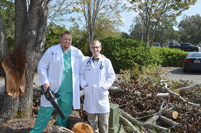 Dr. Loader and Dr. Philipp stand beside the tree they just cut down after the hurricane.