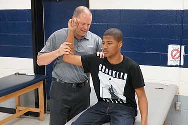 Dr. William Greer examines the arm and shoulder of a student-athlete.