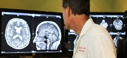 A radiologist reviews a brain scan on his monitor.