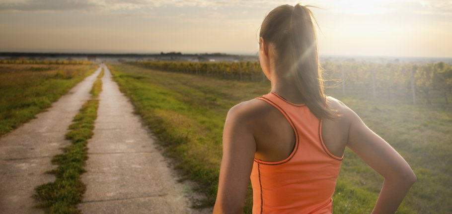 A woman stares at a long path as she gets ready to run.