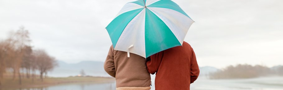 A senior couple stand under an umbrella during a light rain.