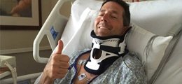 A man with a broken neck gives a thumbs up.