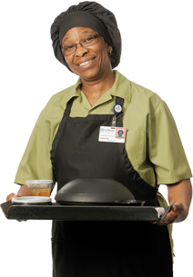 A helpful cafeteria employee smiling with a trey of food.
