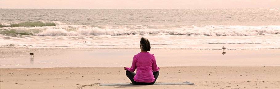 A woman practices yoga outside on the beach.