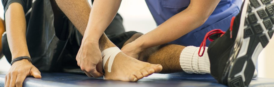 A health care provider assists a patient with a wound.